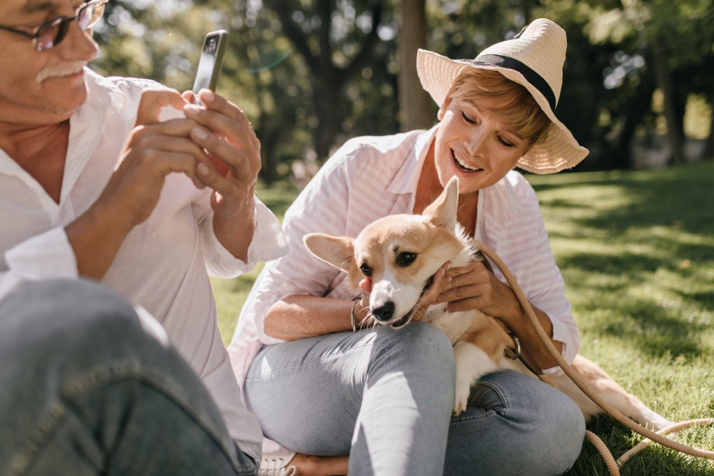 Man taking picture of wife with dog in the park