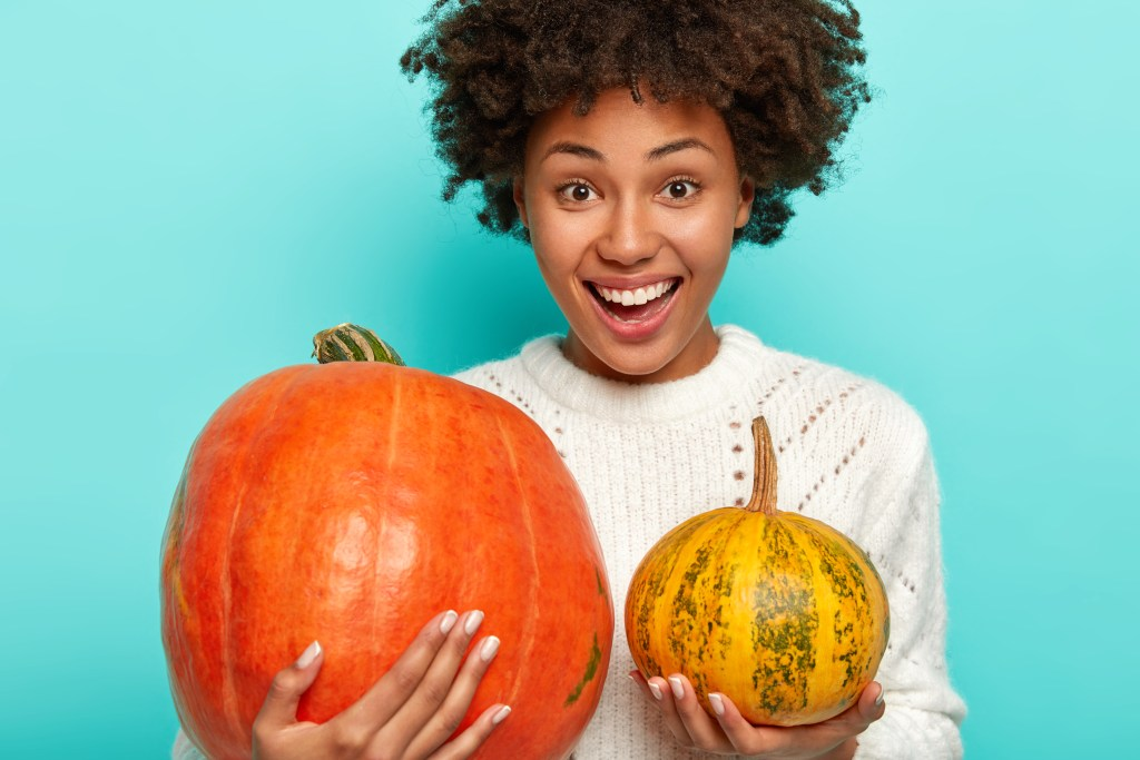 Smiling woman holding two pumpkins.